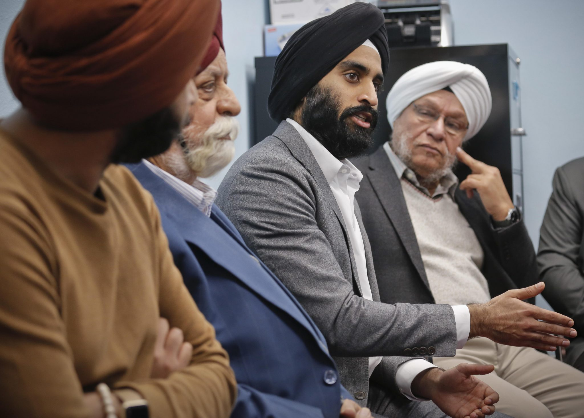 """In this April 9, 2017 photo, Gurwin Ahuja, center, a 27-year-old political operative who helped organize a new awareness campaign to stop attacks against Sikhs, meets with Sikh leaders at the Guru Nanak Darbar house of worship, in Hicksville, N.Y. America's Sikh community is launching a million-dollar nationwide public awareness campaign to help prevent hate attacks against its people. """"Another important motivation is to inspire our young people,"""" said Ahuja. """"To be proud of their values and where they come from."""" (AP Photo/Bebeto Matthews) ORG XMIT: NYBM511"""